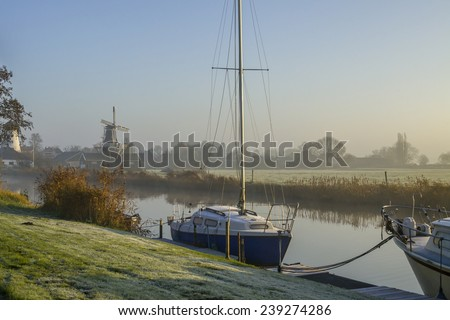 Windmills, boats and water in a typical Dutch countryside at sunrise with fog - stock photo