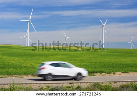 Windmills for electric power production and car, Zaragoza province, Aragon, Spain. - stock photo