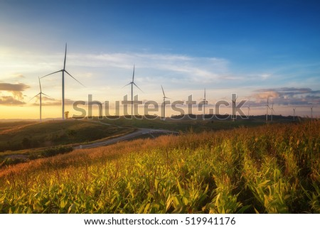 Windmills for electric power production on mountain at sunset.