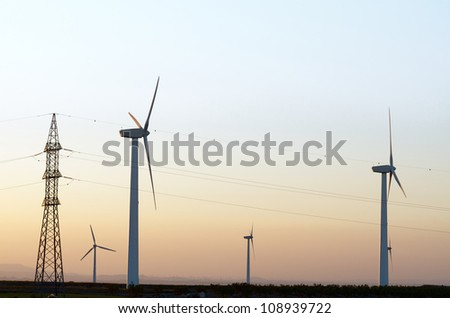 windmills for renewable electric energy production and high voltage tower, La Muela, Zaragoza, Aragon, Spain - stock photo