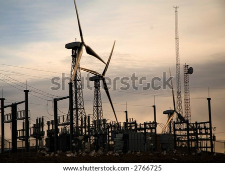 Windmills generating electricity near a substation. - stock photo