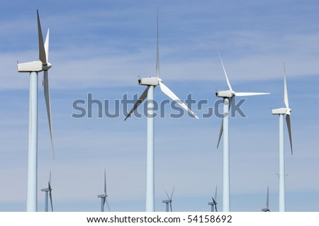 windmills group with cloudy and blue sky - stock photo