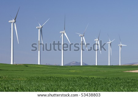 windmills in a field with blue and clear sky - stock photo