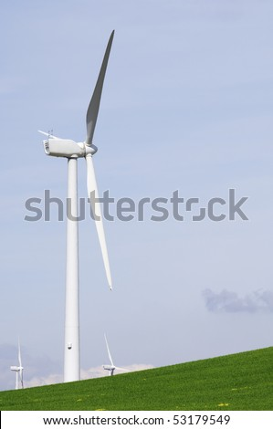 windmills in a green meadow with cloudy sky - stock photo