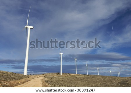 Windmills in a hill with cloudy sky - stock photo