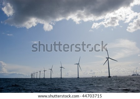 Windmills in a row with cloudy sky - stock photo