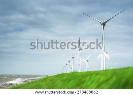 Windmills on a Dutch dike in stormy weather along the IJsselmeer in the noordoostpolder in the Netherlands. The axle height is 135 meter and the wings have a peak height of almost 200 meter. - stock photo