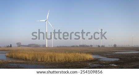 Windmills on a frosted field by the road - stock photo