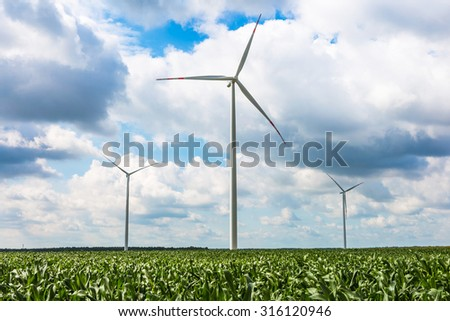 Windmills on corn field under cloudy sky. Beautiful summer landscape photographed in Poland - stock photo