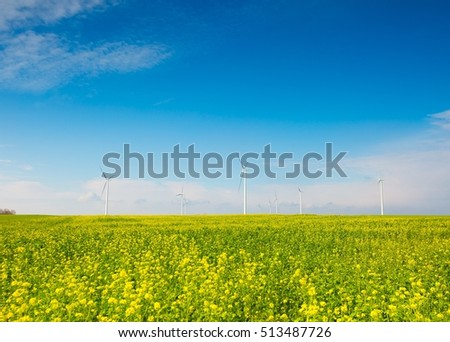Windmills on green field under blue sky. Autumnal or spring landscape.