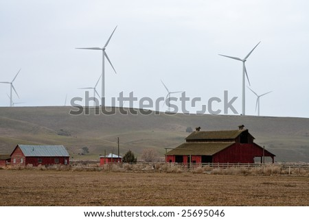 Windmills on hill overlooking some old red buildings.