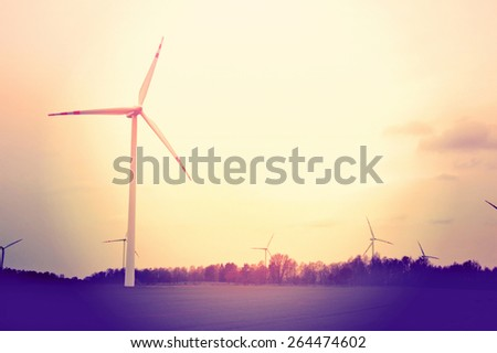 Windmills on the field. Vintage instagram picture. Alternative energy.