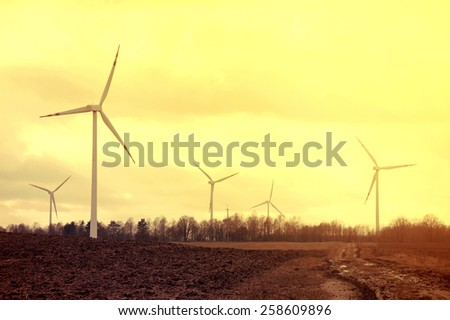 Windmills on the plowed field. Vintage instagram picture. Alternative energy.