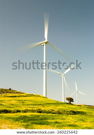 Windmills  power turbine generators  generating electricity from wind on an idyllic landscape in Cyprus. Concept of alternative energy. Note: Some noise visible due to ND filters - stock photo