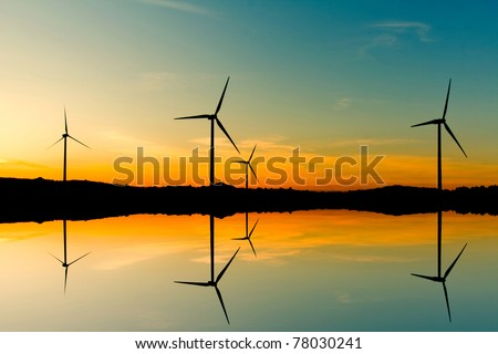 Windmills silhouette on suset background - stock photo