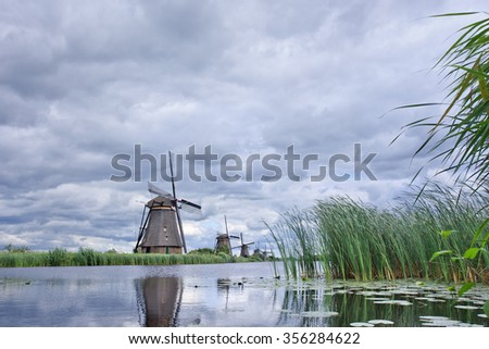 Windmills with dramatic shaped clouds reflected in a canal, Kinderdijk in The Netherlands - stock photo