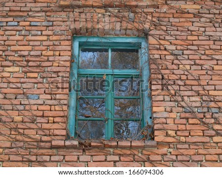 window and front of an old brick house - stock photo
