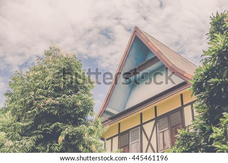 window and house roof in garden against blue sky. Image is vintage effect and low light photo
