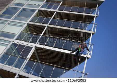 Window cleaner hanging in a rope washing windows in a modern waterfront apartment house - stock photo