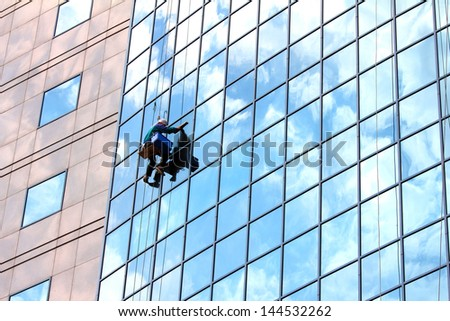 window cleaner hanging on rope at work on skyscraper