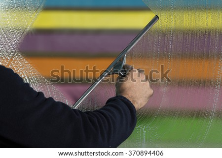 Window cleaner using a squeegee to wash a window - stock photo