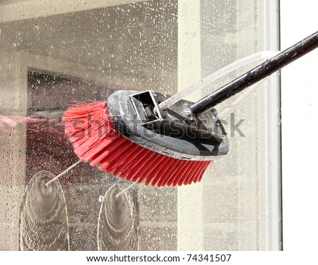 window cleaning using a reach and wash system. The cleaning brush is used to clean glass windows by using pure water so it does not leave streaks on the glass. - stock photo