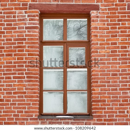 Window covered with frost-work in brick wall - stock photo