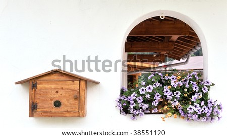 window decorated with flowers and mail box on the white wall - stock photo