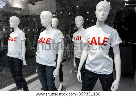 Window display with five mannequins wearing t-shirts with text Sale - stock photo
