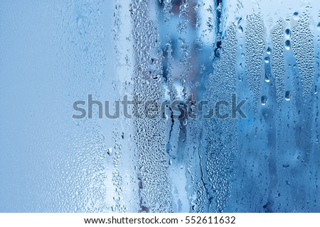 Window glass with condensation, strong, high humidity in the room, large water droplets flow down the window, cold tone, natural water drops on window