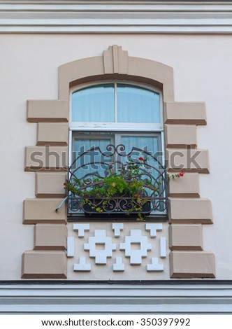 Window in a classic style and a box of flowers. Architecture - stock photo