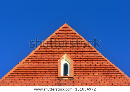 window in a roof attic with bricks against blue sky with triangle shape - stock photo