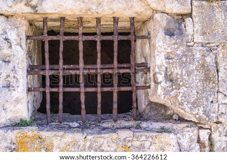 window lattice from old rusty iron on a stone wall of ancient dungeon or a prison - stock photo