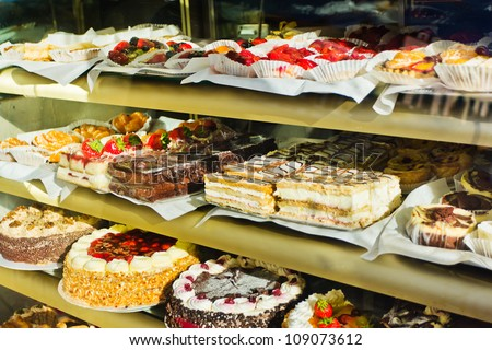 Window of a cake shop with a variety of cakes on display - stock photo