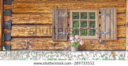 Window of an old wooden cottage with pot plant. - stock photo