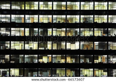 window of the multi-storey building of glass and steel office lighting and working people within - stock photo