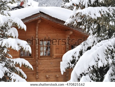 window on a wooden cottage facade in the firs snowing