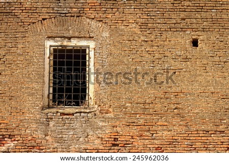 window on old abandoned castle wall, red weathered bricks facade - stock photo