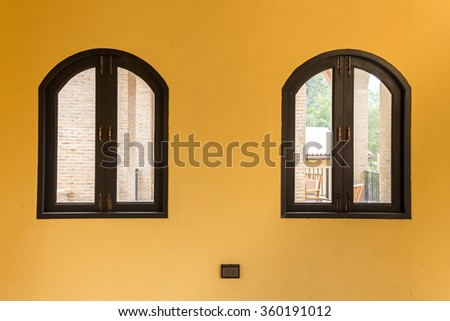window on the yellow wall with electricity plug