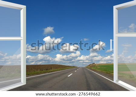 window opened to the asphalted road and cloudy blue sky - stock photo