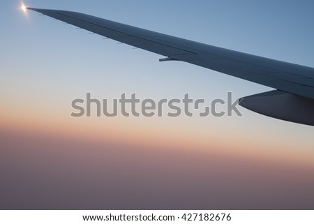 Window seat view of aircraft wings while flying against blue orange sky for conceptual background with soft focus - stock photo