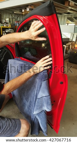 window tinting a red car - stock photo