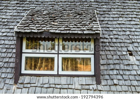 Window under roof tile of old house  - stock photo