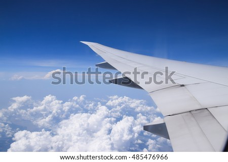 window view from airplane , wing and blue sky background