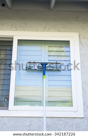 Window washer uses a sponge and squeegee on a pole to wash the exterior windows of a home. - stock photo