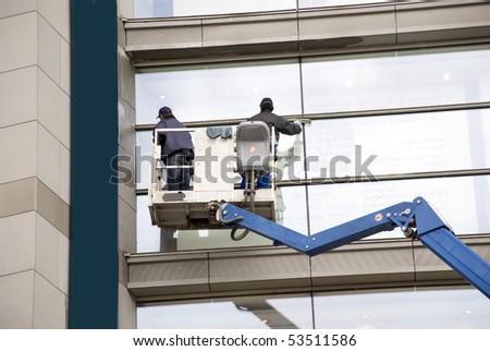 window washers on a hydraulic ramp - stock photo