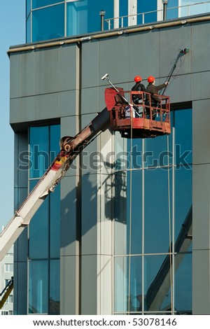Window washing on high-rise office building in crane beam - stock photo