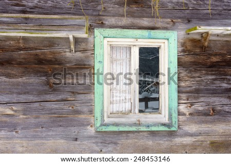 Window with a green border in a wooden wall