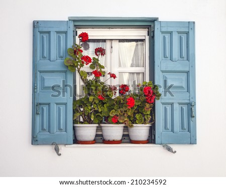 Window with blue shutters and potted geraniums against white background Mediterranean window of a home in the Greek islands. - stock photo