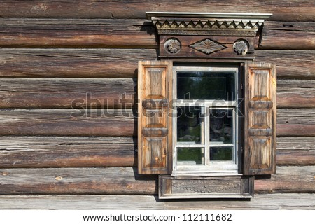 Window with casings in an old wooden house made ??of logs